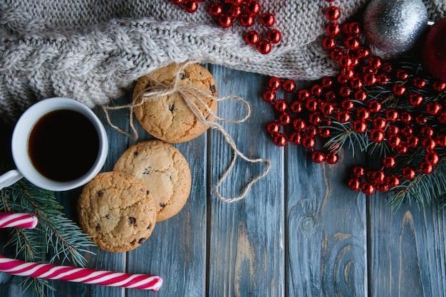Arredamento accogliente vacanza calda su sfondo di legno. spirito natalizio e atmosfera festosa. maglione lavorato a maglia e perline rosse con una tazza di caffè caldo e biscotti con gocce di cioccolato.