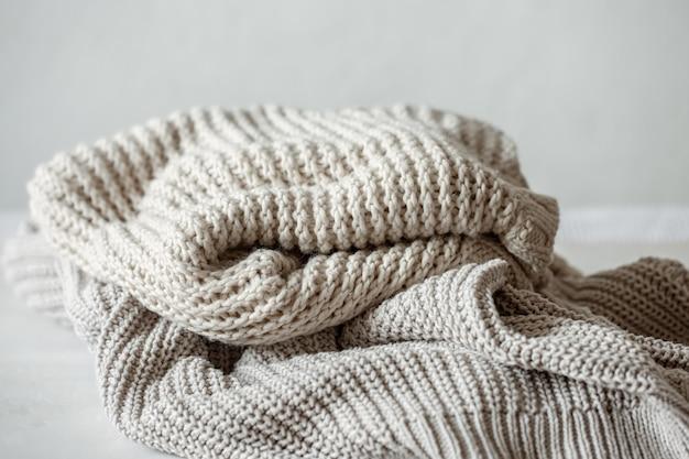Maglioni lavorati a maglia accoglienti e caldi in primo piano di colori pastello.