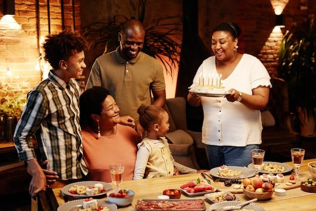 Accogliente ritratto dai toni caldi di felice famiglia afroamericana che festeggia il compleanno insieme al chiuso ogni...