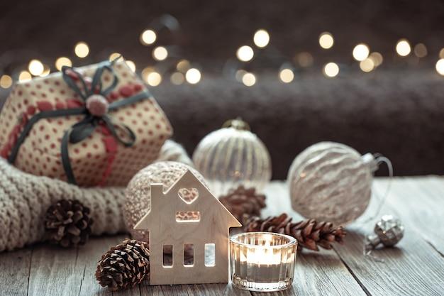 Sfondo invernale accogliente con dettagli decorativi su sfondo scuro sfocato con bokeh.