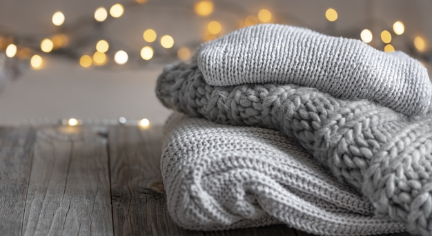 Accogliente sfondo invernale con una pila di maglioni lavorati a maglia e luci spazio copia
