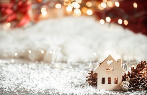 Accogliente sfondo natalizio invernale con bokeh e dettagli in legno su uno sfondo chiaro.