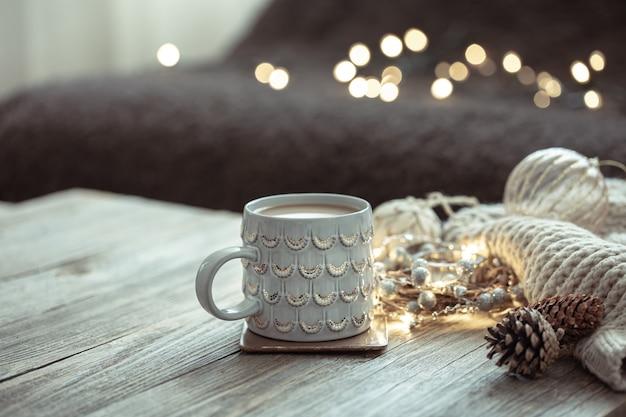 Accogliente composizione invernale con una tazza e dettagli decorativi su uno sfondo sfocato.