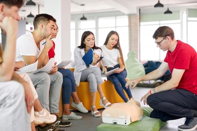 Classe di rcp con istruttore maschio che parla e dimostra il primo soccorso