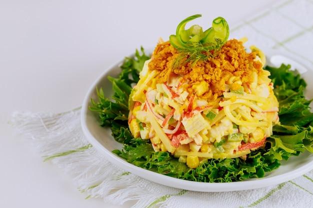 Insalata di polpa di granchio con formaggio di mais dolce e uova decorate con chips di mais e cetriolo