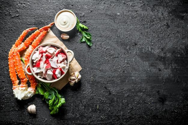 Polpa di granchio con salsa, erbe aromatiche e spicchi d'aglio. su sfondo nero rustico