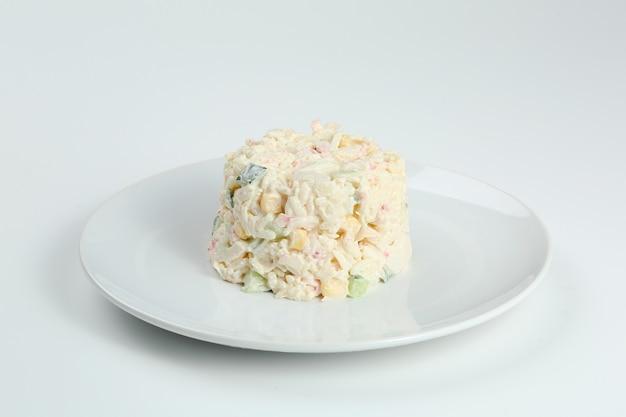 Insalata di granchio con riso sul primo piano bianco del piatto con lo spazio della copia. insalata tradizionale russa con bastoncini di granchio isolati su bianco