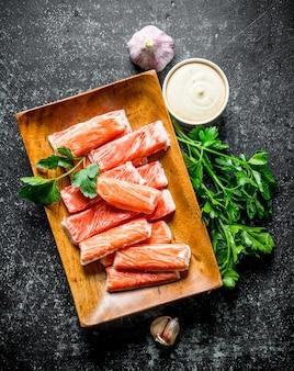 Bastoncini di granchio con aglio, erbe aromatiche e salsa. su fondo rustico scuro