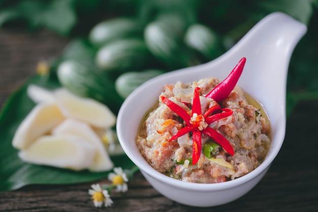 Uova di granchi in noce di cocco chili dip con le verdure sulla tavola di legno
