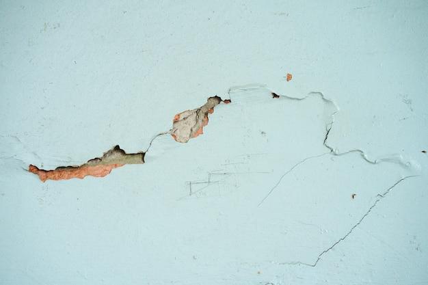 Crepa su un muro di cemento dipinto di blu