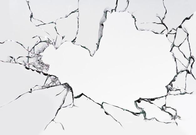 Vetro rotto incrinato su una superficie bianca