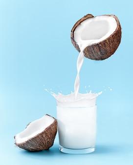 Cocco incrinato con schizzi di latte. il latte di cocco viene versato nel bicchiere.