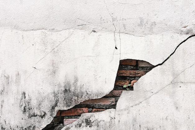Muro di cemento incrinato coperto con superficie di cemento grigio come sfondo.