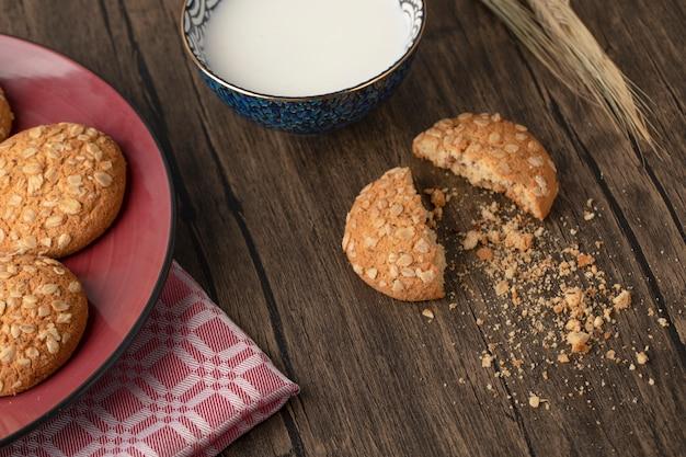 Biscotti di farina d'avena incrinati con semi e ciotola di latte fresco sulla tavola di legno