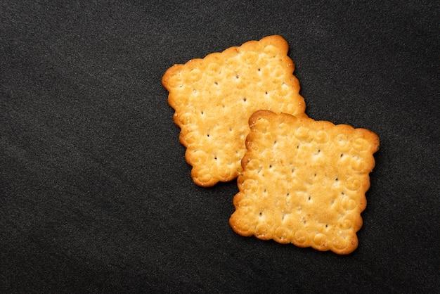 Cracker con sesamo su sfondo nero.