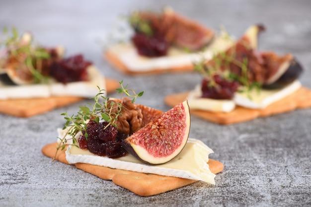 Cracker con fetta di marmellata di camembert fichi e noci un'ottima idea snack per una vacanza