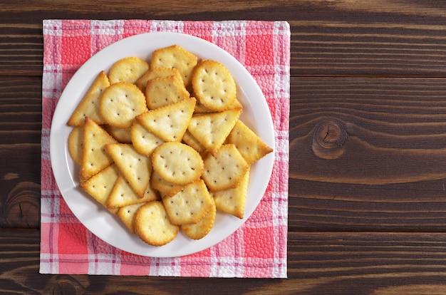 Biscotti cracker con sapore di formaggio in piatto su tavola di legno, vista dall'alto