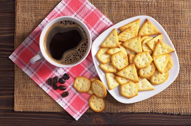 Cracker al sapore di formaggio e tazza di caffè sul tavolo di legno, vista dall'alto