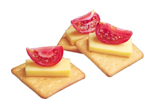 Cracker con formaggio e pomodoro isolati su sfondo bianco