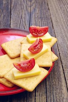 Cracker con formaggio e pomodoro su un vecchio tavolo di legno