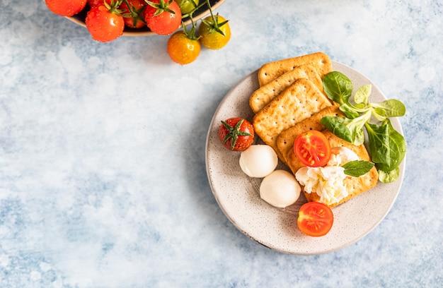 Crackers con insalata verde di pomodorini e mozzarella