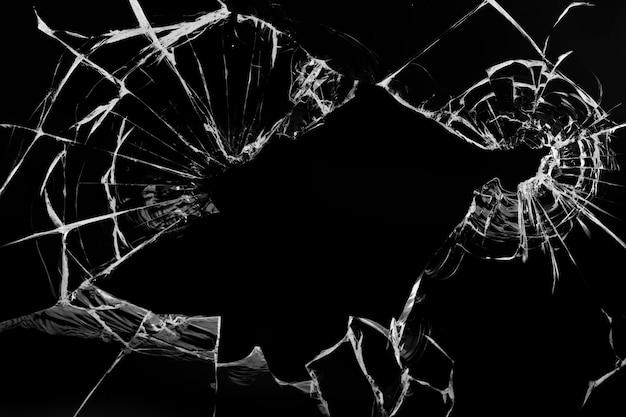 Crepe nel vetro, con fori di proiettili su una superficie nera