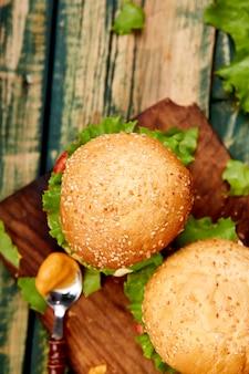 Mestiere l'hamburger di manzo sulla tavola di legno isolata su fondo nero.