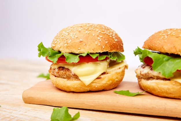 Hamburger di manzo artigianale sulla tavola di legno su sfondo chiaro