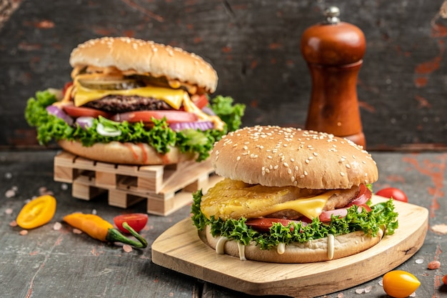 Hamburger di manzo artigianale con verdure su fondo di legno rustico. fast food e concetto di cibo spazzatura
