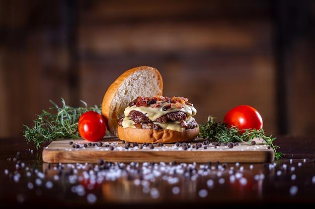 Hamburger di manzo artigianale con formaggio, pancetta e salsa su fondo in legno