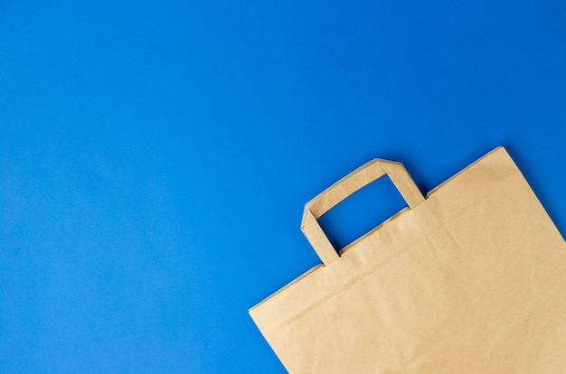 Sacchetto di carta marrone artigianale con manici su sfondo blu. banner piatto, vista dall'alto, spazio copia, zero rifiuti, articoli senza plastica. pacchetto mockup eco, consegna o concetto di shopping online