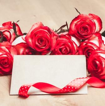 Biglietto artigianale con rose rosse e nastro per gli auguri