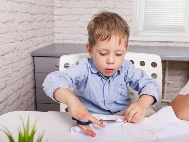 Artigianato per bambini che tagliano con le forbici e la carta per incollare