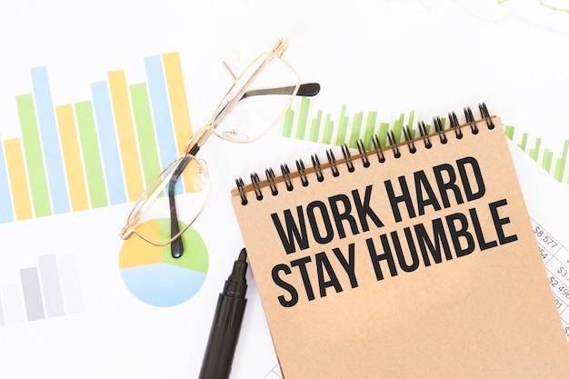 In un taccuino a colori artigianale c'è un'iscrizione work hard stay humble, accanto a matite, bicchieri, grafici e diagrammi.