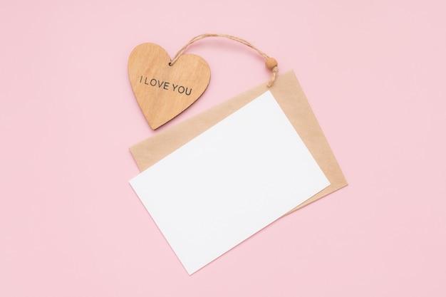Busta artigianale, carta bianca di carta bianca e cuore di legno con le parole ti amo su uno sfondo rosa