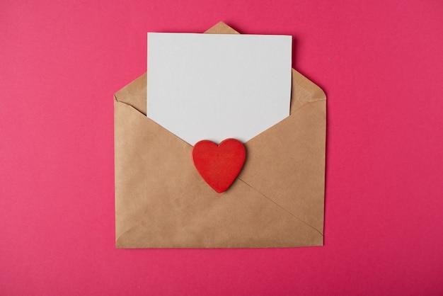 Busta artigianale con un foglio bianco all'interno e un cuore rosso su sfondo rosa caldo
