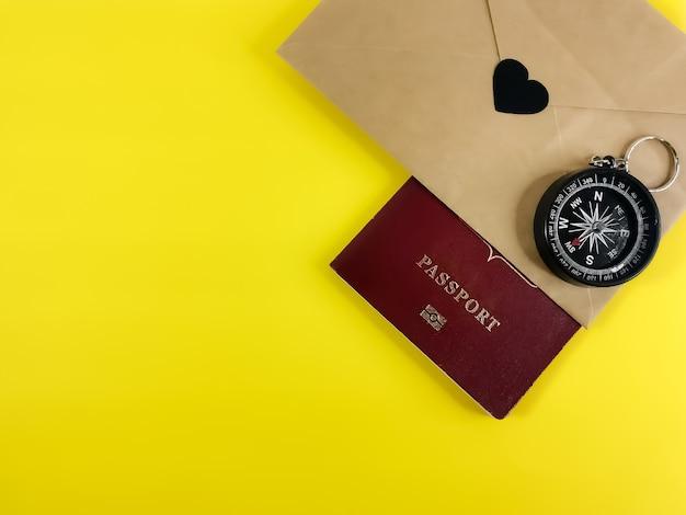 Una busta artigianale con un cuore e una bussola manuale e un passaporto su un giallo