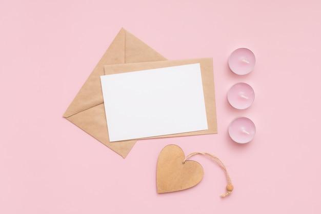Buste artigianali, cartoncino bianco di carta bianca, candele rosa e cuore di legno su sfondo rosa