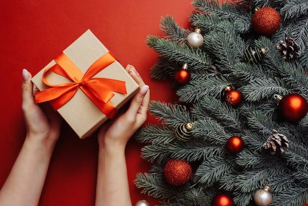 Regalo artigianale con un nastro rosso nelle mani di una giovane ragazza con una manicure nuda accanto ai rami di un albero di natale.