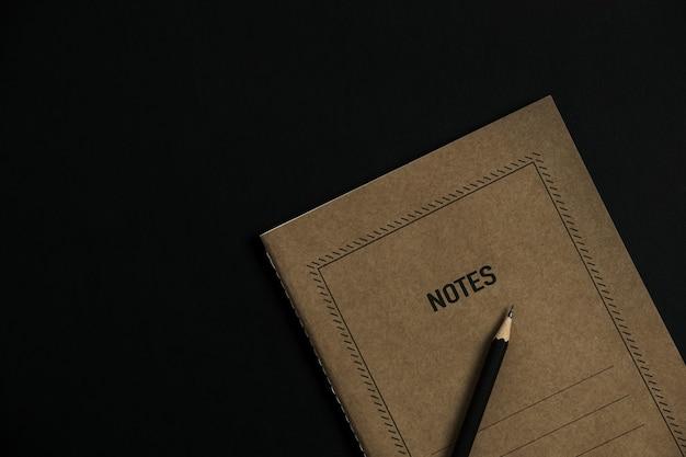 Foglio di quaderno artigianale, matita, clip su nero