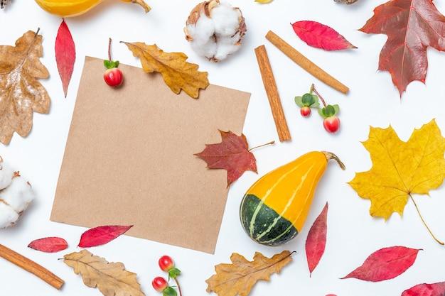Cornice vuota di carta artigianale e foglie autunnali, cotone, zucca, sfondo di cannella. modello autunnale. composizione autunnale, concetto di caduta. disposizione piatta, vista dall'alto e spazio di copia