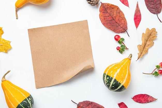 Cornice vuota di carta artigianale e foglie d'autunno, zucca, sfondo. modello autunnale. composizione autunnale, concetto di caduta. disposizione piana, vista dall'alto e spazio di copia. note adesive.