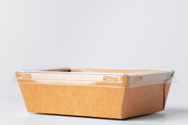 Scatola di carta usa e getta artigianale con coperchio in plastica su grigio, copia spazio