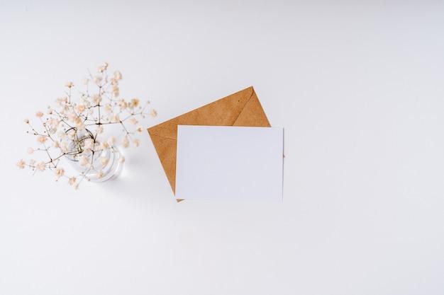Busta di carta artigianale con nota bianca vuota all'interno su bianco. vista piana laico e dall'alto. lettera d'amore romantica con fiori