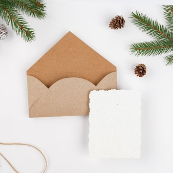 Busta in carta artigianale con rami di abete, pigne e carta bianca