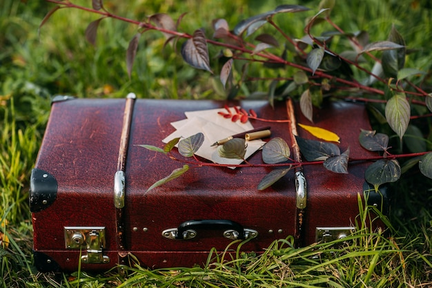 Buste di carta artigianale e penna stilografica dorata sulla valigia vintage