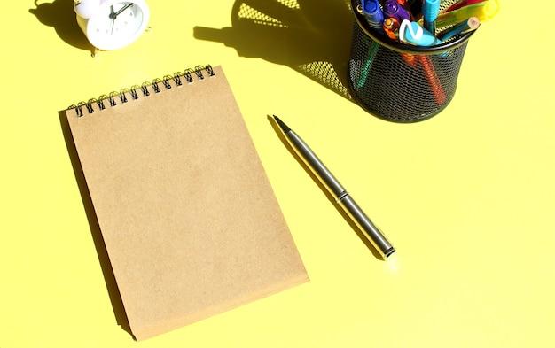 Taccuino di carta artigianale con spazio vuoto per testo con cancelleria. colore di sfondo giallo. concetto di affari.