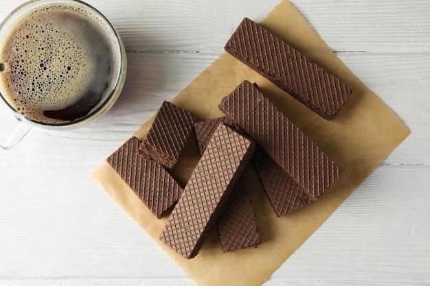 Mestiere la carta con i wafer e la tazza di caffè su fondo di legno bianco, vista superiore
