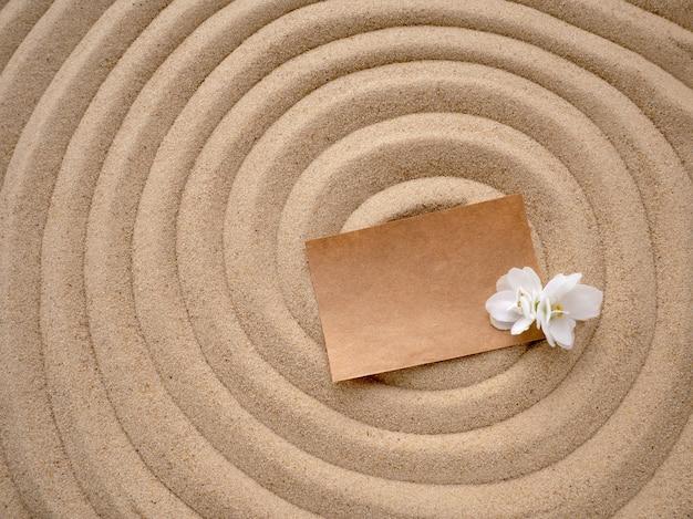 Carta artigianale con un fiore bianco sulla trama della sabbia marina.