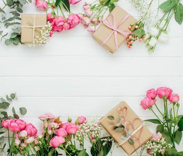 Scatole regalo e fiori di incarto della carta del mestiere su fondo di legno bianco con spazio vuoto per testo. vista dall'alto, piatto.